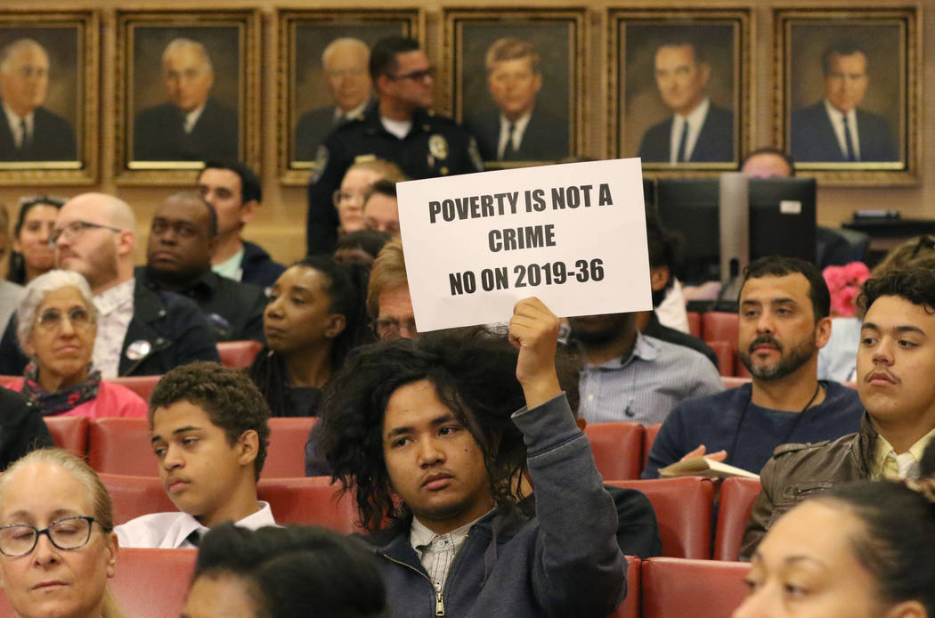 Rudolf Jovero of Las Vegas holds a sign inside council chambers during a protest against the ci ...