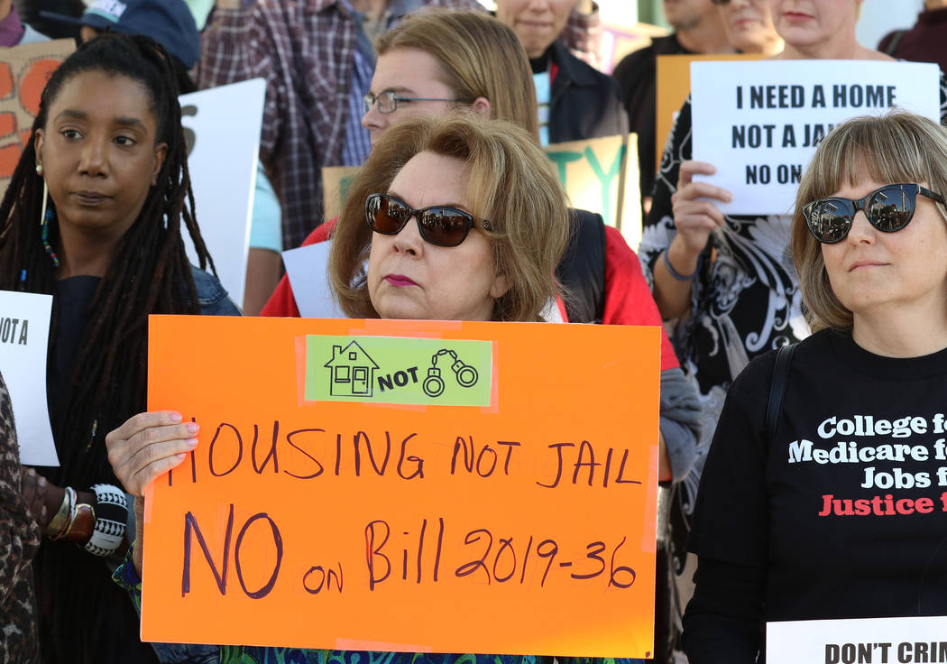 Eva Love, left, and Deidre Radford of Las Vegas hold signs outside Las Vegas City Hall as they ...