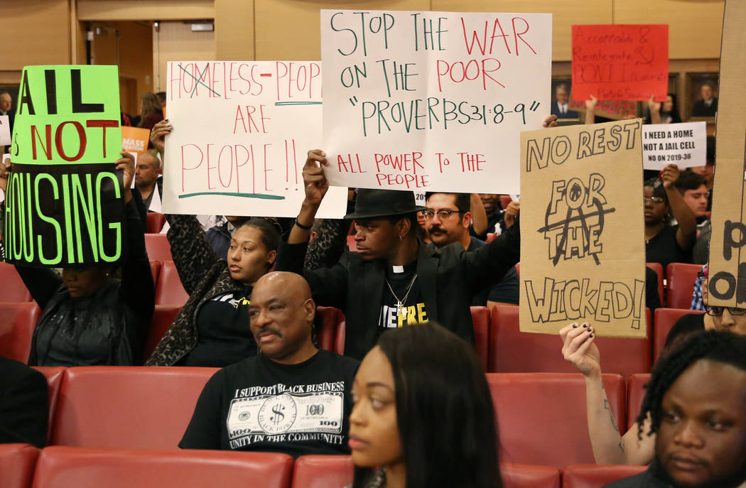 Protesters hold signs inside council chambers during a protest against the city council's contr ...