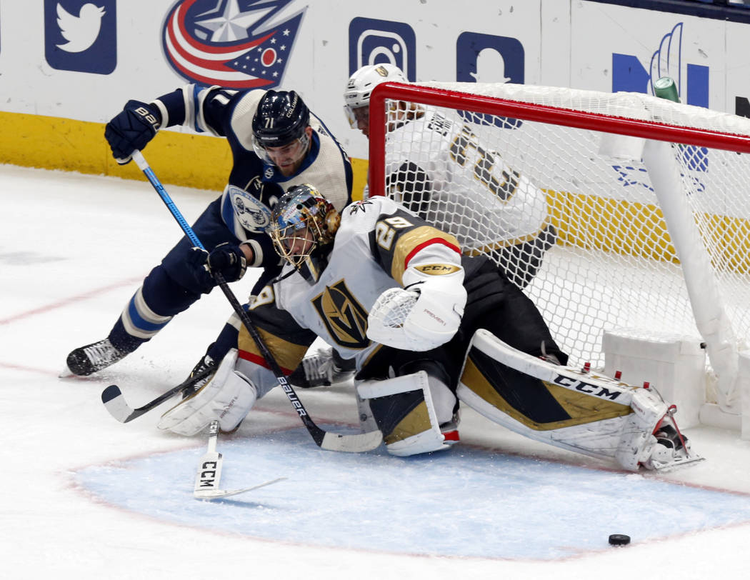 Vegas Golden Knights goalie Marc-Andre Fleury, right, stops a shot by Columbus Blue Jackets for ...