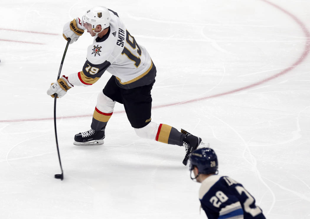 Vegas Golden Knights forward Reilly Smith, left, shoots the puck in front of Columbus Blue Jack ...