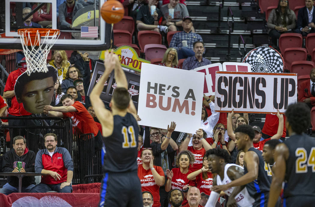 UNLV Rebels fans do their best to distract Purdue Fort Wayne forward Dylan Carl (11) while shoo ...
