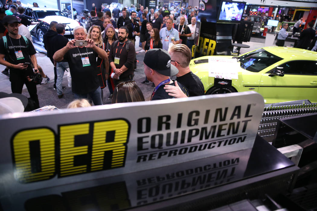 People visit the Original Equipment Reproduction booth during the SEMA show at the Las Vegas Co ...