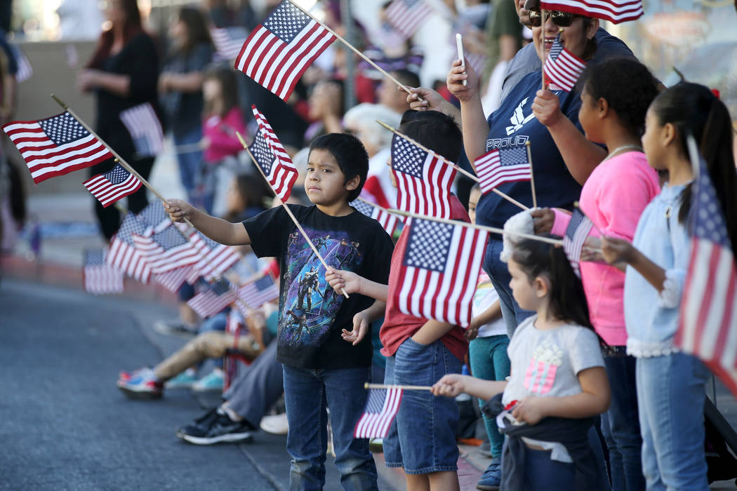 Spectators, including Nick Camocho, 9, left, wave American flags during the Veterans Day Parade ...