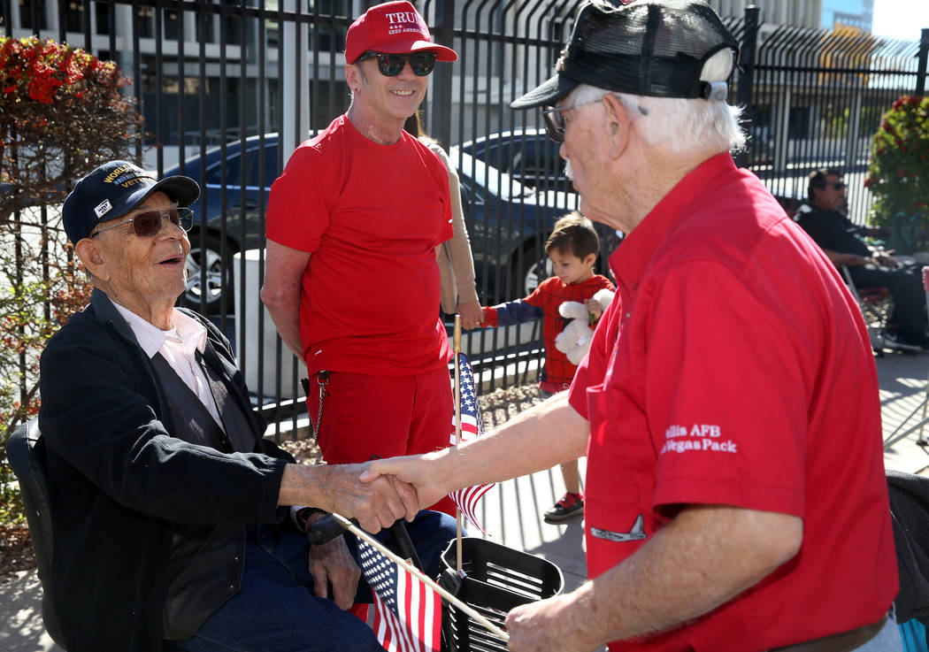 Don Harten, 80, thanks Robert Jensen, 96, and his son David Jensen, 63, in the Veterans Day Par ...