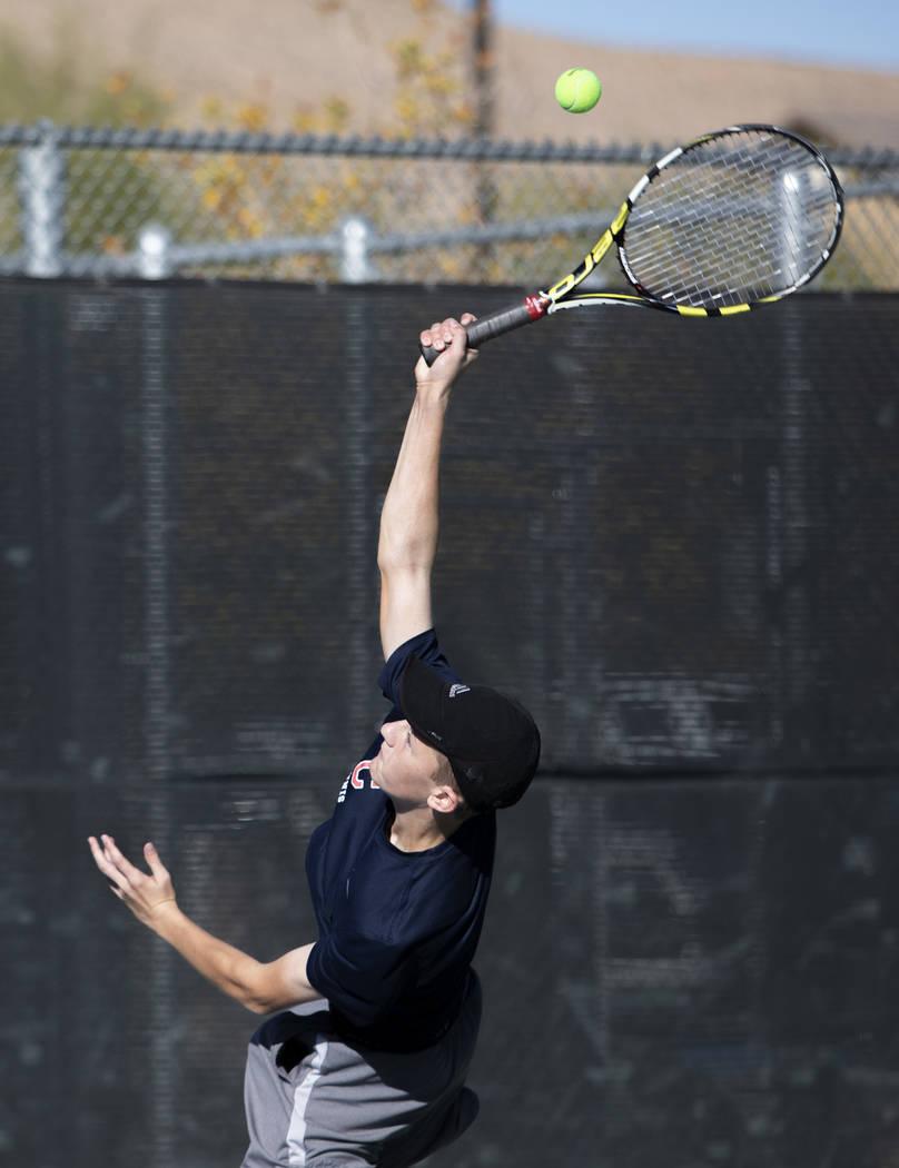Coronado High School's Jonah Blake serves during a doubles match with his partner Jason Michael ...