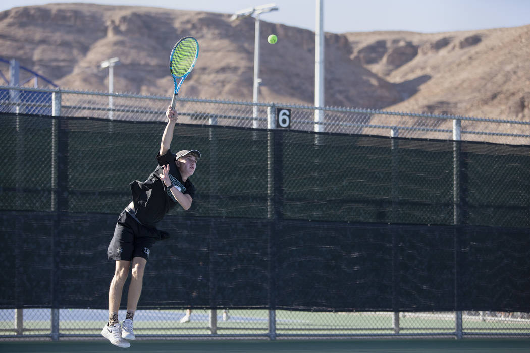 Palo Verde High School's Benjamin Waid jumps to serve during a doubles match with his partner W ...