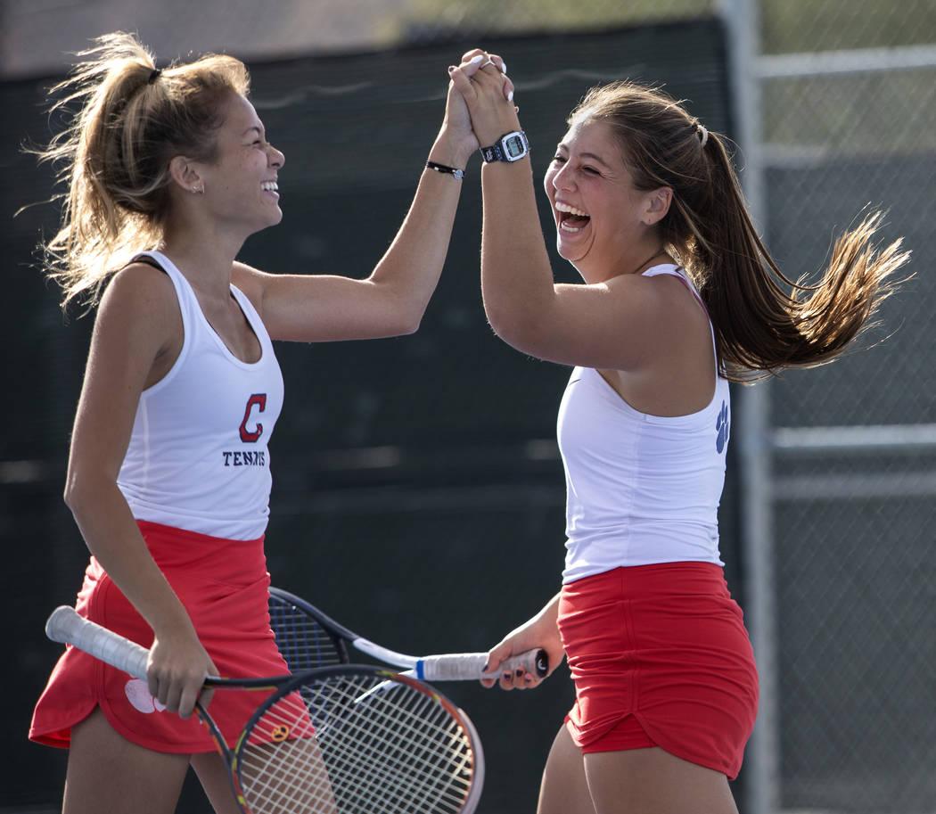 Coronado's Sofia Potomitis celebrates with her doubles partner Ava Nhiasi as they score a point ...