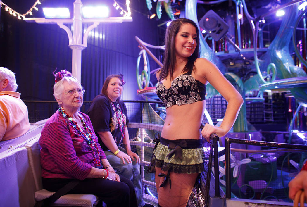 Violet Perkins, left, watches as performer Molleigh Wallace, right, and other performers board ...