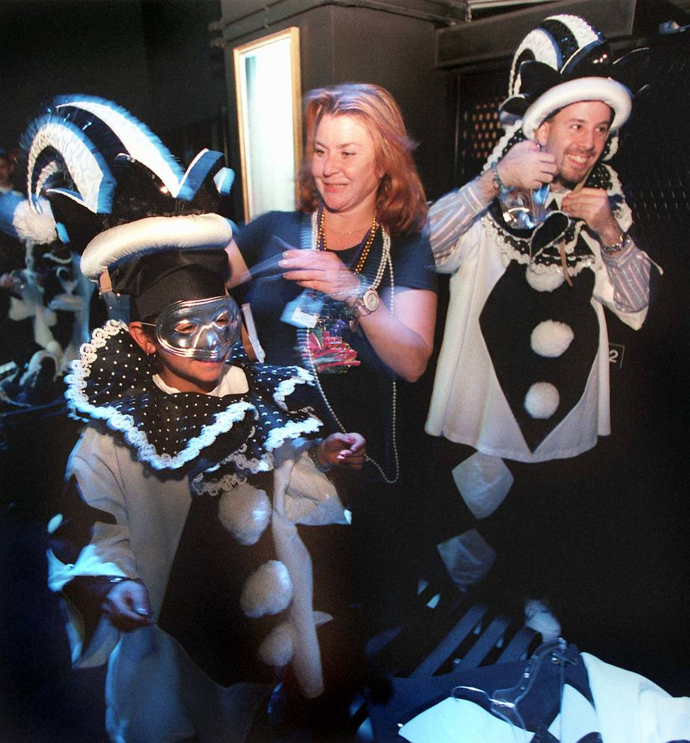 Carol Windish of the Rio helps guests Lauren Martinez and Marc Adler with their costumes as the ...
