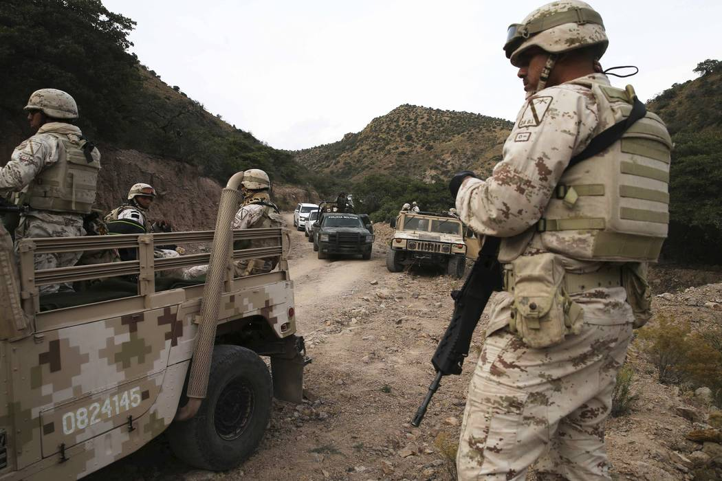 Heavily armed Mexican authorities guard a caravan of friends and relatives of the LeBaron famil ...