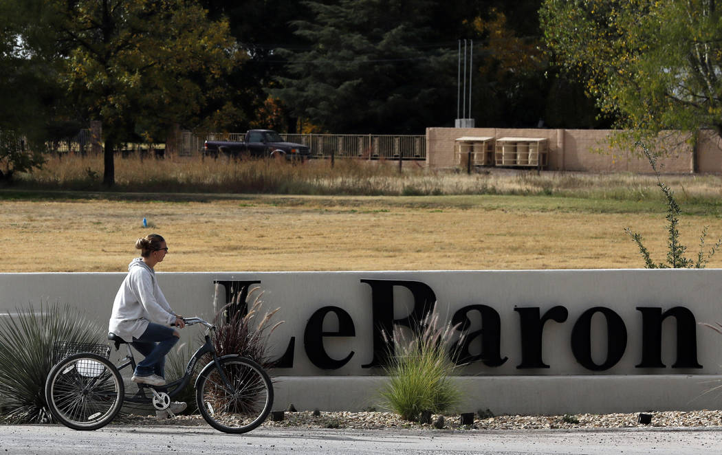 A woman cycles past a sign announcing the Colonia LeBaron, a community settled by members of th ...