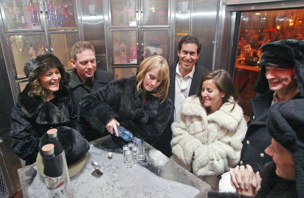 Vodka host Kelly Reid, center, pours shots of ZYR vodka to a fur-clad group from Atlanta, Ga., ...
