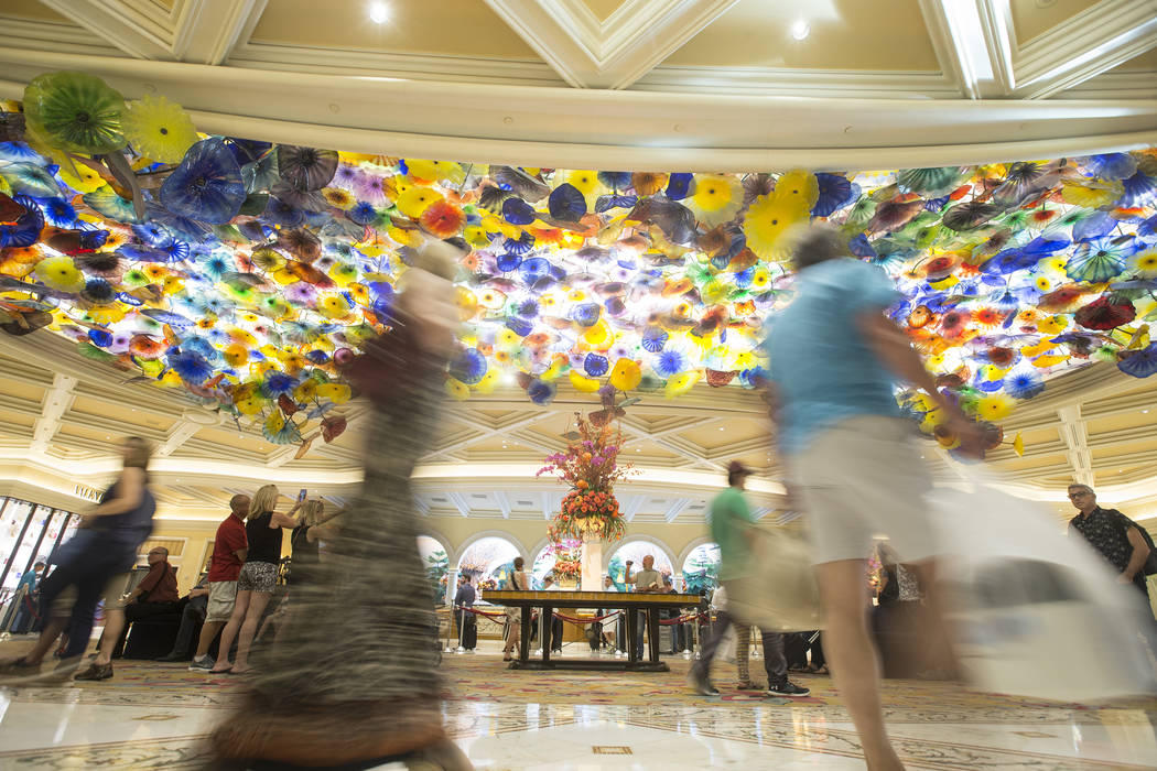 Patrons pass by the Chihuly Fiori de Como glass sculpture in the lobby of Bellagio in Las Vegas ...