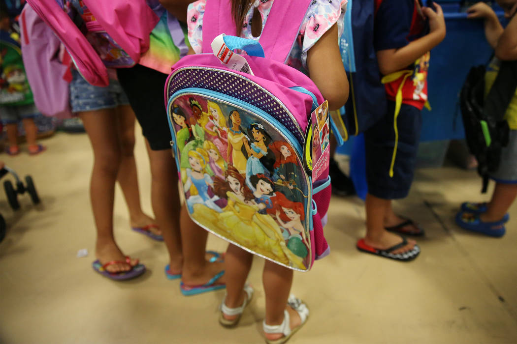 Foster children receive school supplies including a backpack during an event sponsored by Foste ...