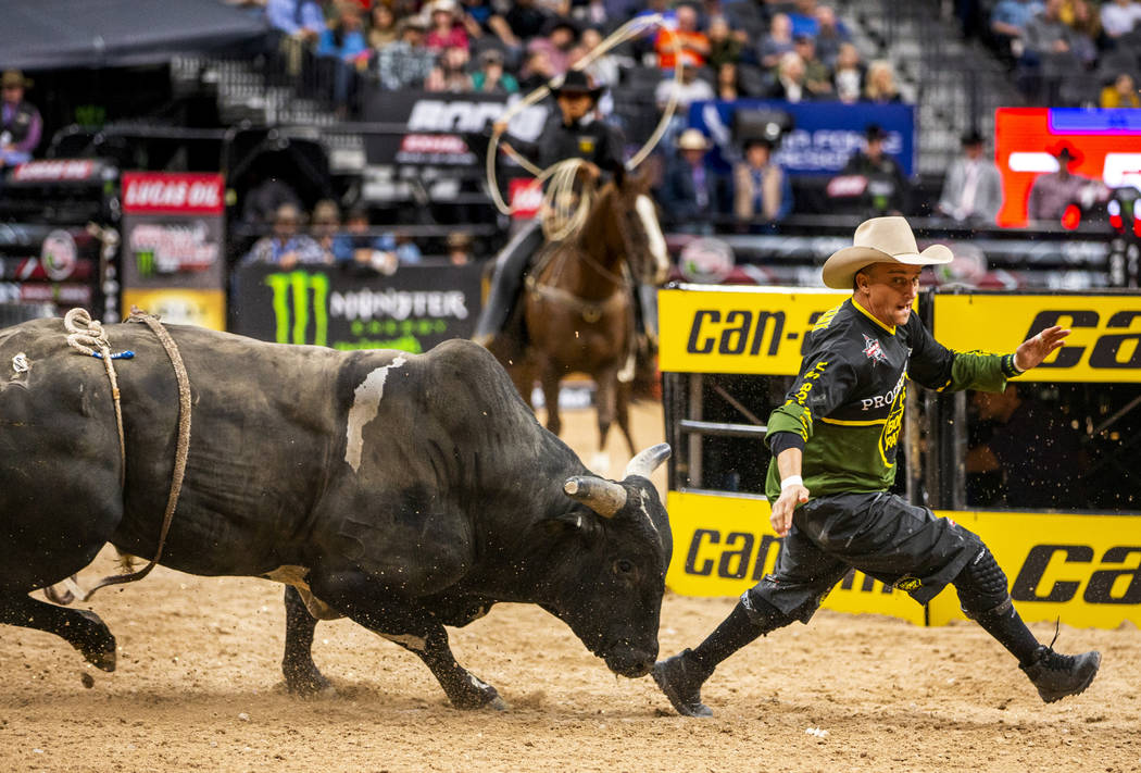Bullfighter Frank runs to escape the horns of a bull during the PBR World Finals at T-Mobile Ar ...