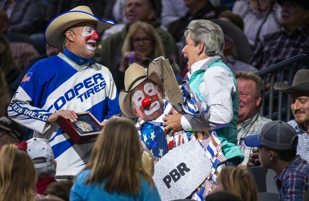 Rodeo clown Flint Rasmussen trades a fan a belt buckle for a jacket during the PBR World Finals ...