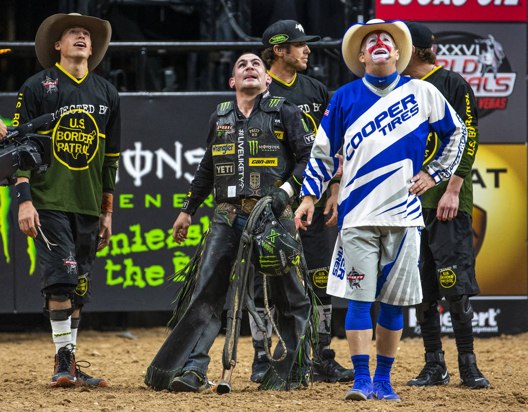 Chase Outlaw, center, watches the replay above to see he rode the eight seconds needed atop of ...