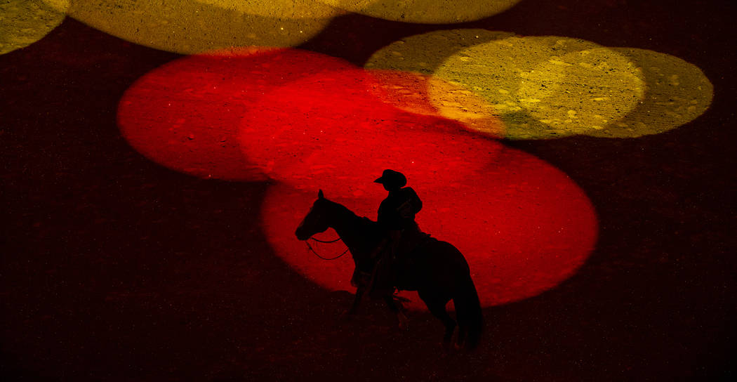 Safety man Derrick Begay is bathed in colored lights as during the opening ceremonies of PBR Wo ...