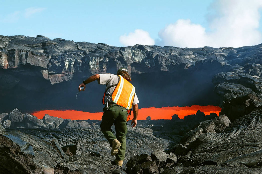 FILE--Ranger Arnold Nakata from Hawaii Volcanoes National Park approaches a skylight in a lava ...