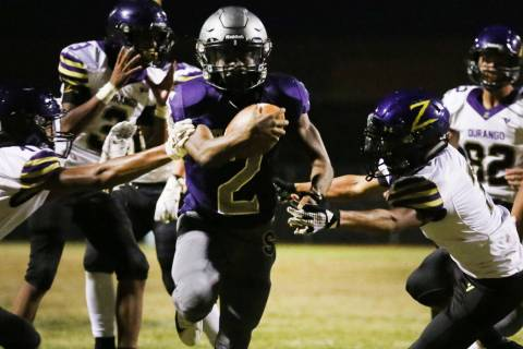 Silverado High's running back Aginae Cunningham (2) scrambles away from Durango High defense as ...