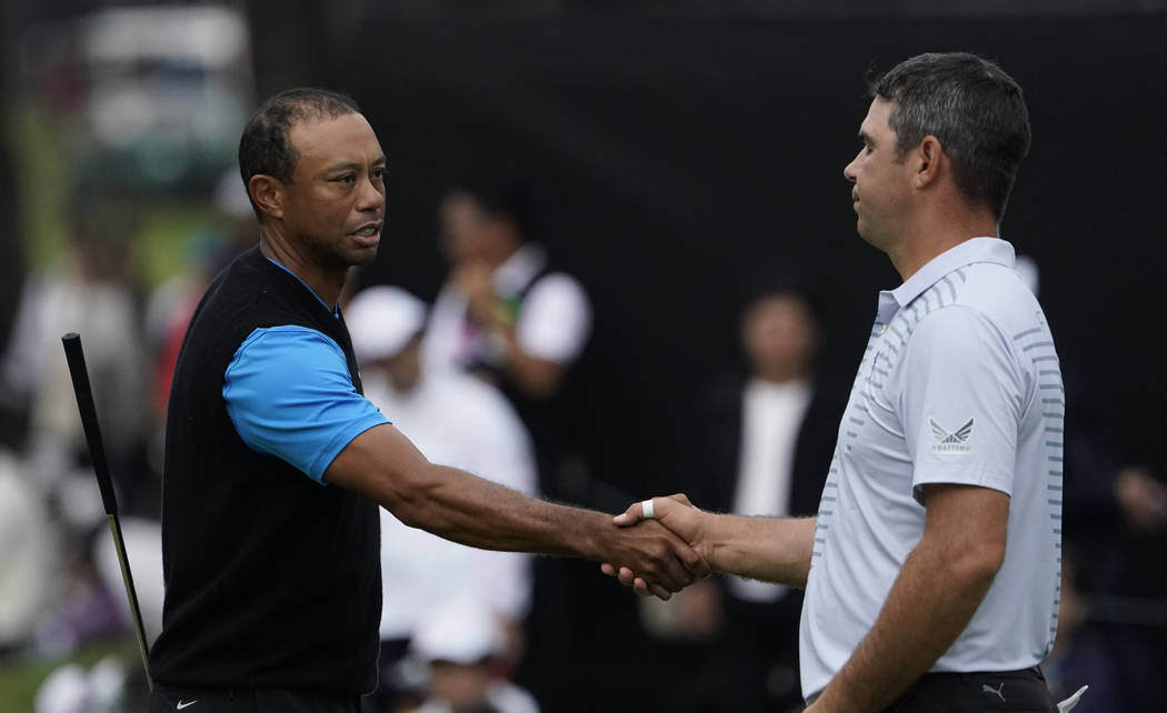 Tiger Woods of the United States, shakes hands with Gary Woodland of the United States on the18 ...