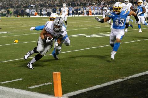 Oakland Raiders running back Alec Ingold (45) runs toward the end zone to score past Los Angele ...