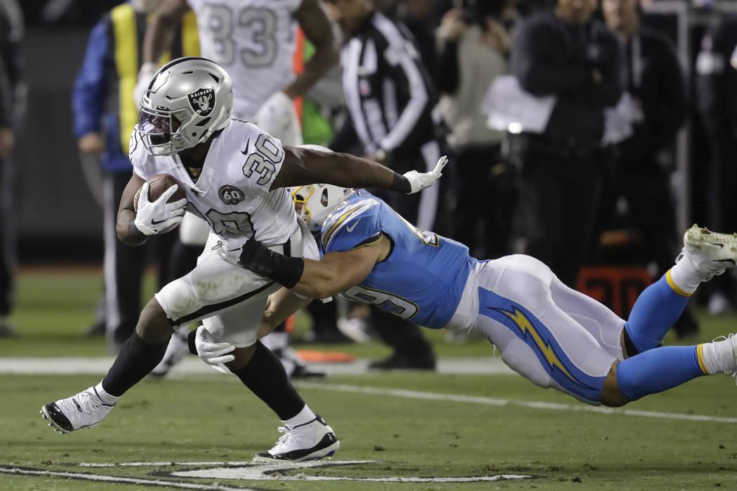 Oakland Raiders running back Jalen Richard (30) runs against Los Angeles Chargers linebacker Dr ...