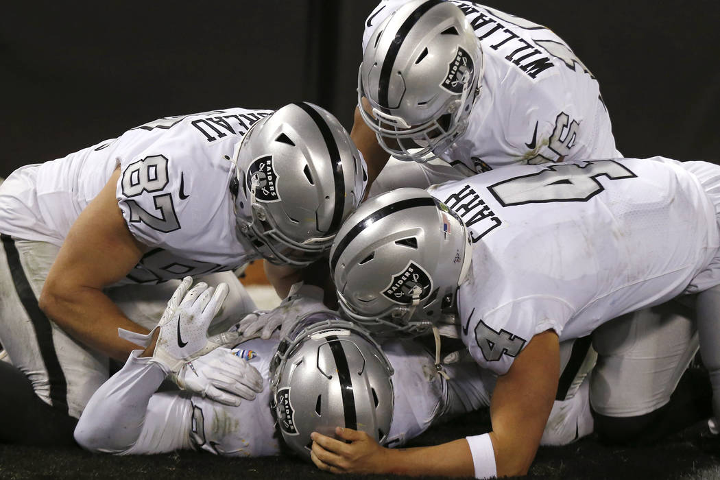 Oakland Raiders running back Josh Jacobs, bottom, is congratulated by teammates after scoring a ...