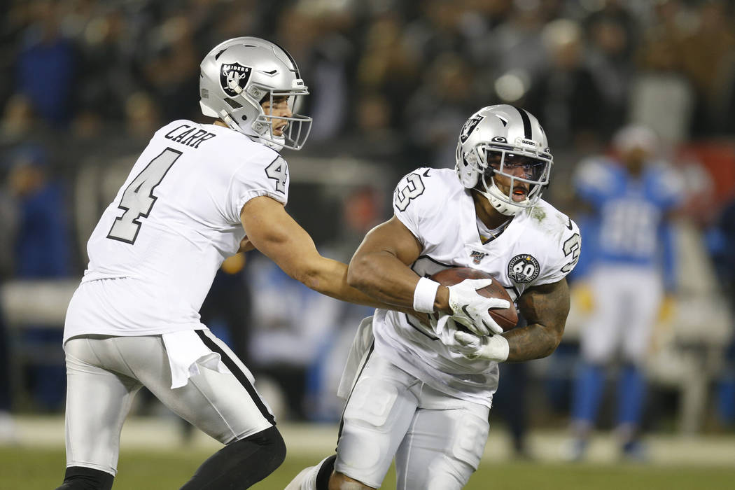 Oakland Raiders quarterback Derek Carr (4) hands off to running back DeAndre Washington (33) du ...