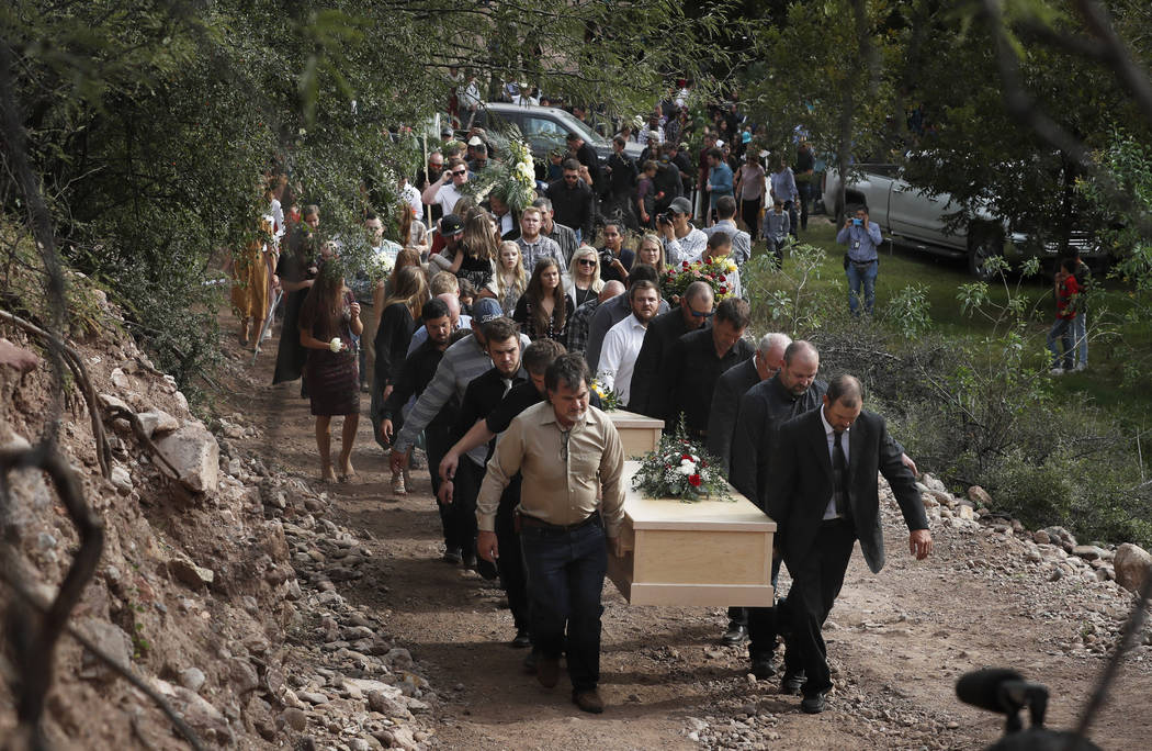 Family and friends carry the coffins that contain the remains of Dawna Ray Langford, 43, and he ...
