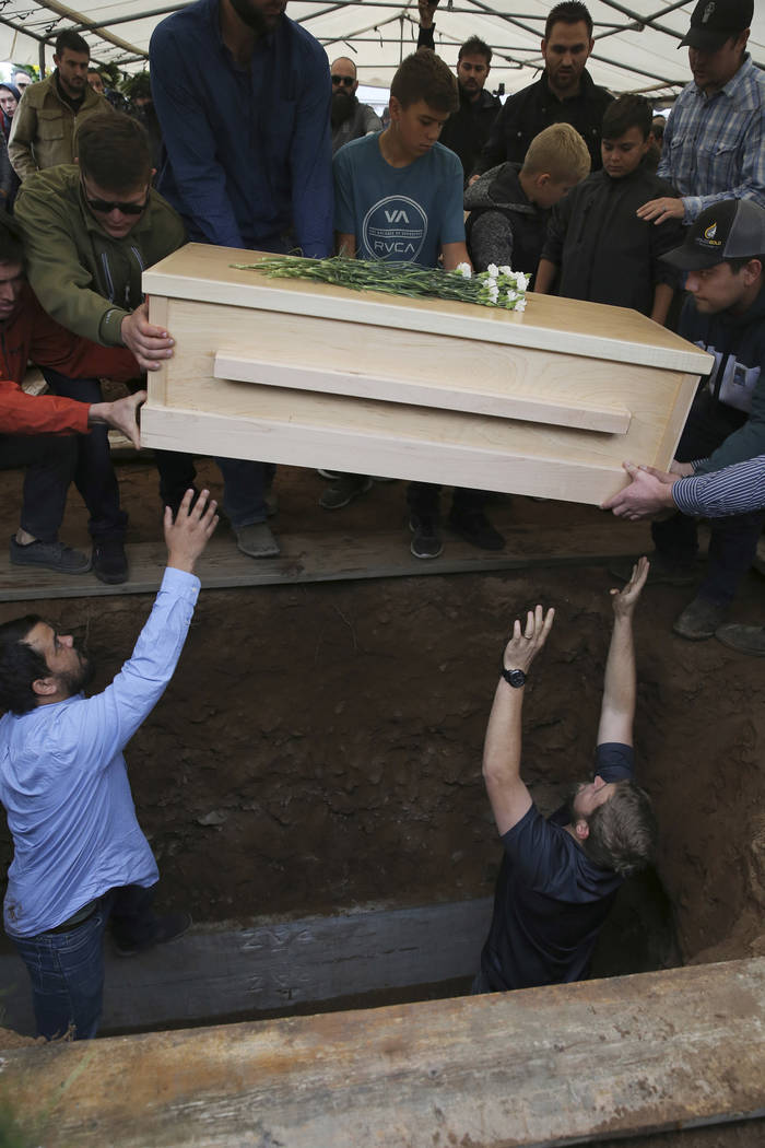 The coffin that contains the remains of 12-year-old Howard Jacob Miller Jr. is lowered into a g ...