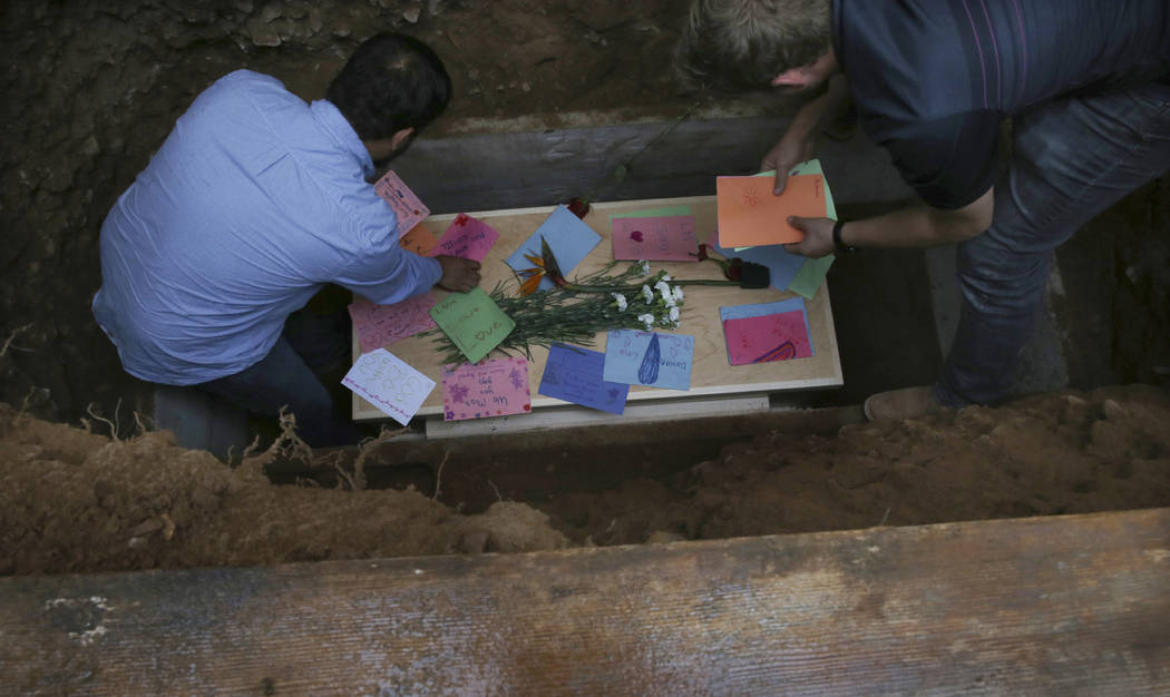 Men arrange personal notes on the coffin that contains the remains of 12-year-old Howard Jacob ...