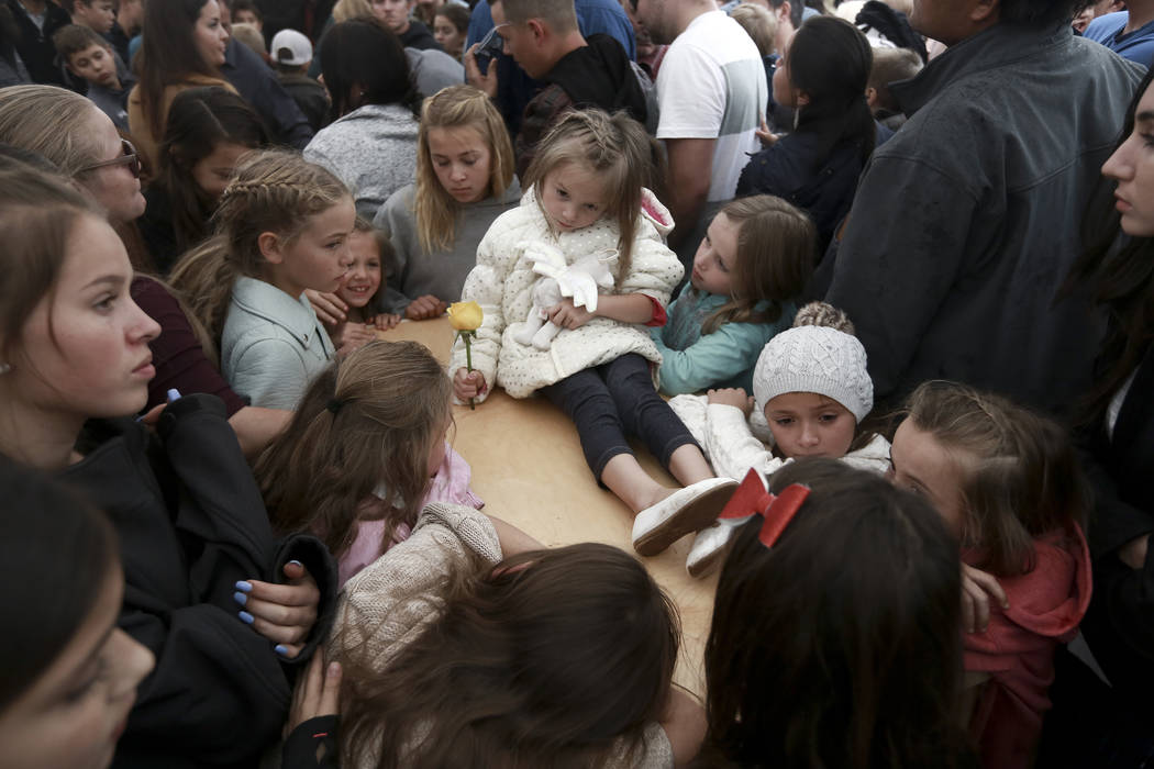 A child sits on top of a coffin as family and friends pay their final respects to Rhonita Mille ...