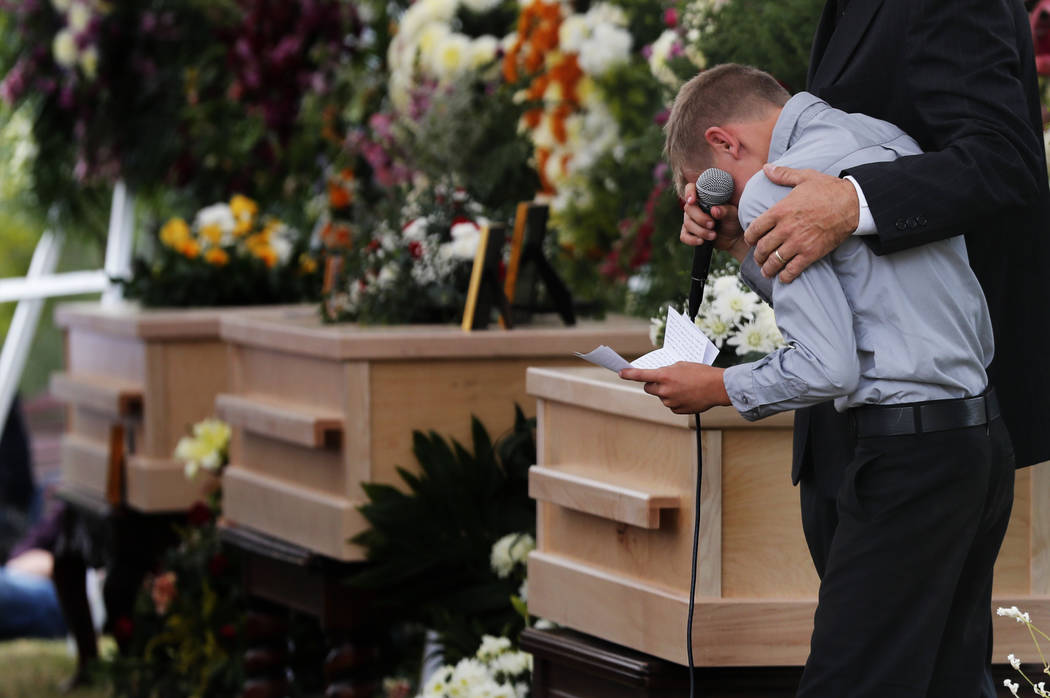 A boy pauses as he speaks next to the coffins of Dawna Ray Langford, 43, and her sons Trevor, 1 ...
