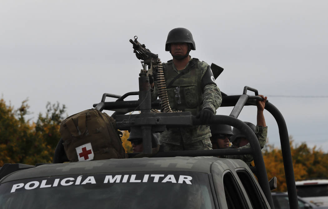 Mexican soldiers stand guard as Dawna Ray Langford, 43, and her sons Trevor, 11, and Rogan, 2, ...