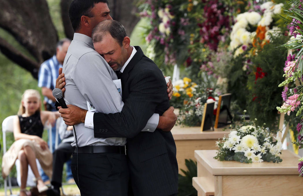 Men embrace next to the coffins of Dawna Ray Langford, 43, and her sons Trevor, 11, and Rogan, ...