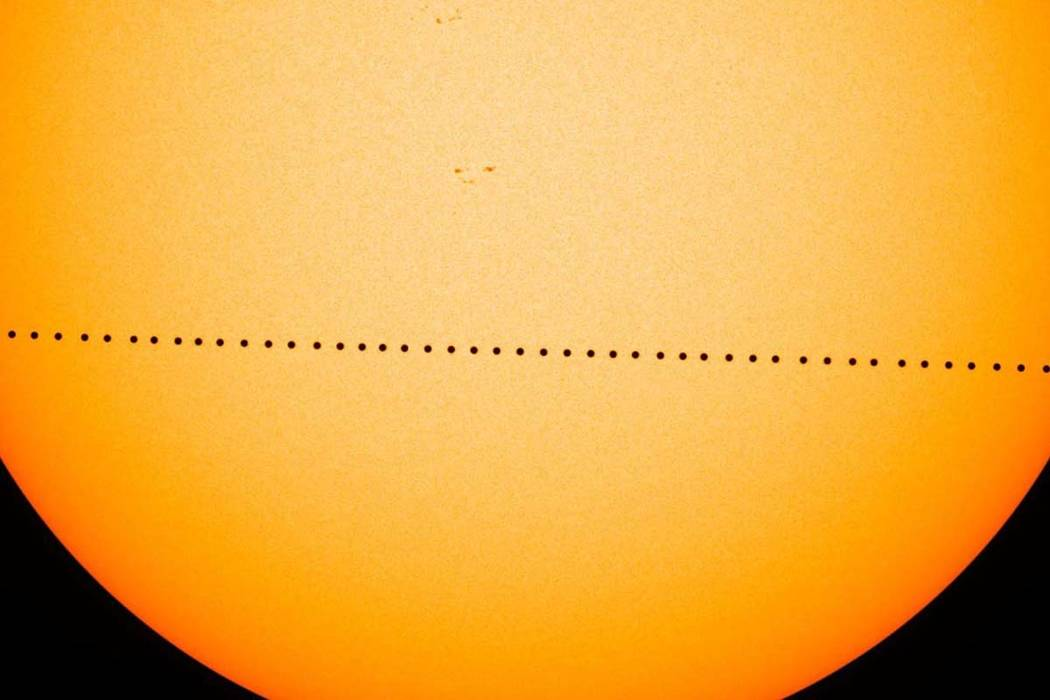 In a composite image provided by NASA, the planet Mercury passes directly between the sun and E ...