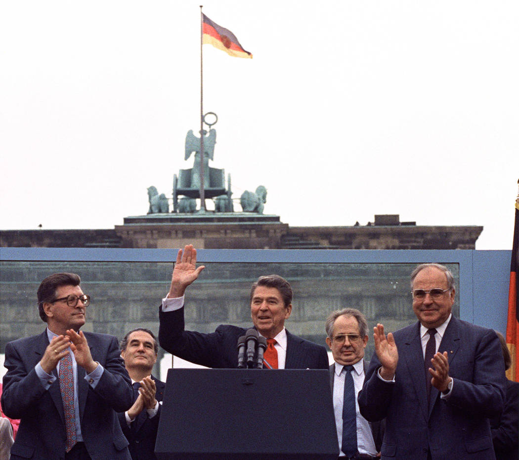 FILE - In this on Friday, June 12, 1987 file photo, U.S. President Ronald Reagan acknowledges t ...