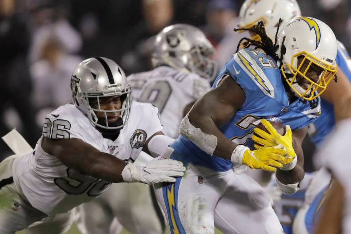 Los Angeles Chargers running back Melvin Gordon, right, carries as Oakland Raiders defensive en ...