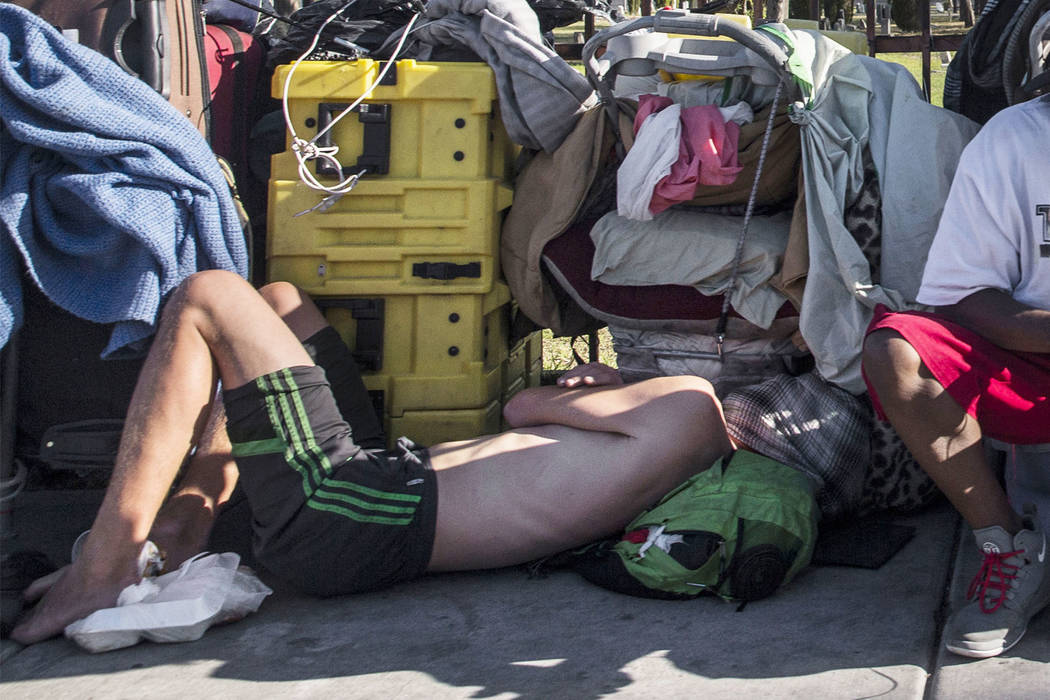 In this May 3, 2018, file photo, a man sleeps on the ground on East Owens Avenue in Las Vegas. ...