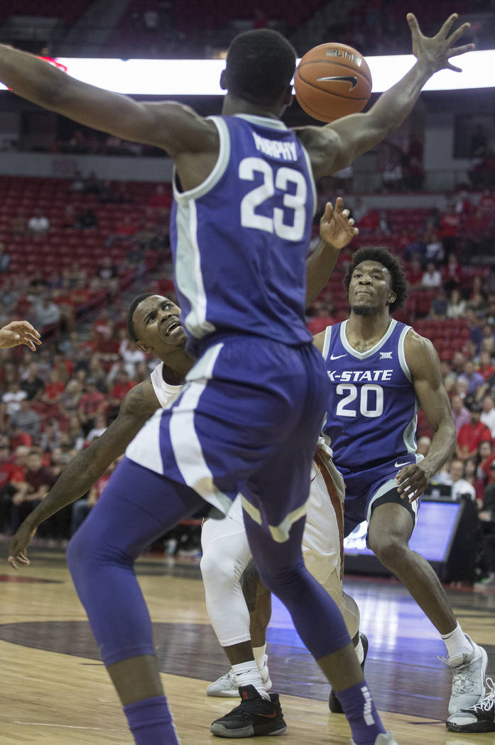 UNLV Rebels guard Amauri Hardy (3) fights for a loose ball with Kansas State Wildcats forward X ...