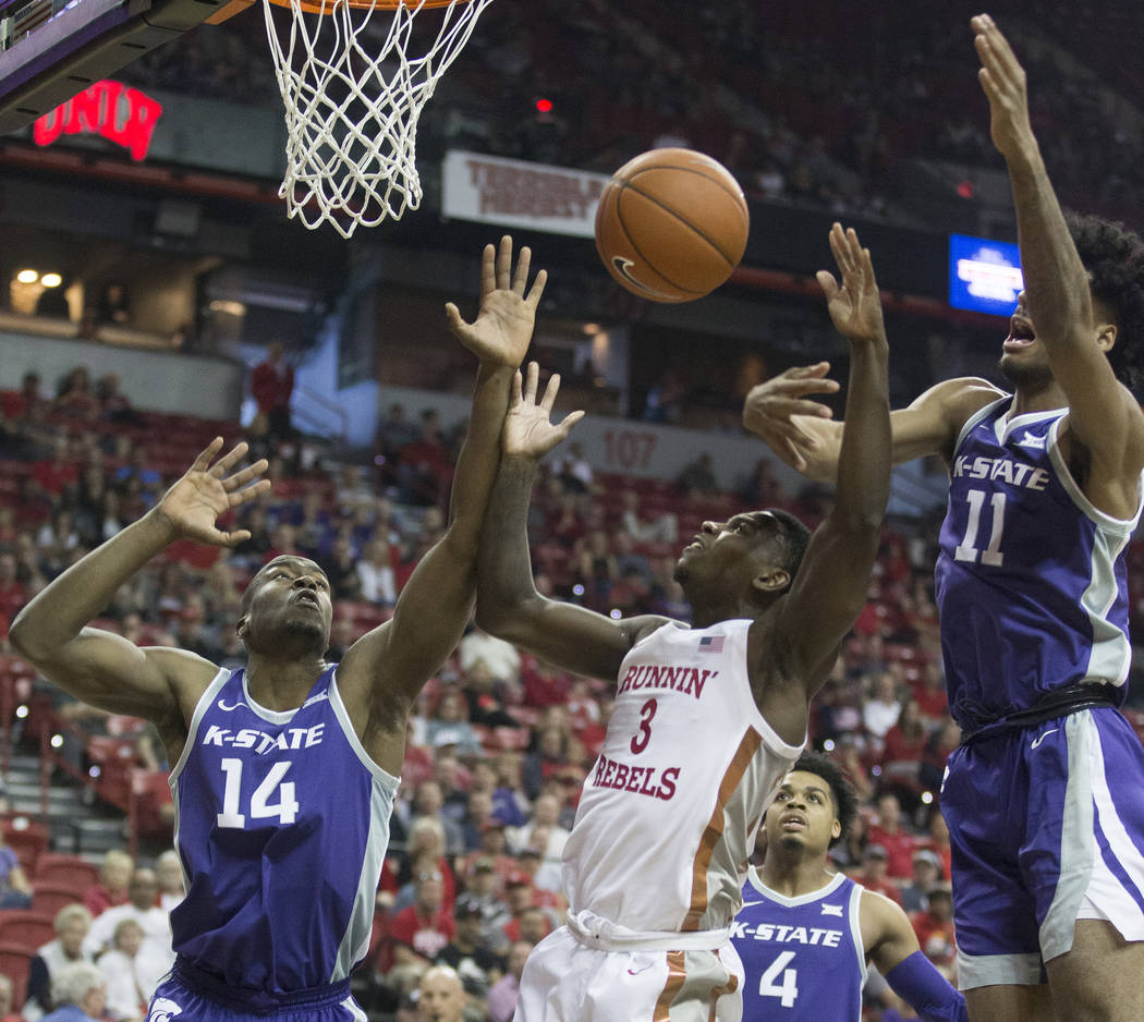 UNLV Rebels guard Amauri Hardy (3) fights for a loose ball with Kansas State Wildcats forward M ...