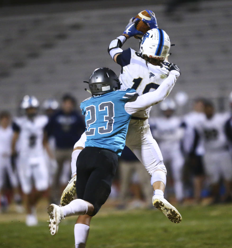 Foothill's Thomas Fisher-Welch (18) catches a pass under pressure from Silverado's Breven Palpa ...