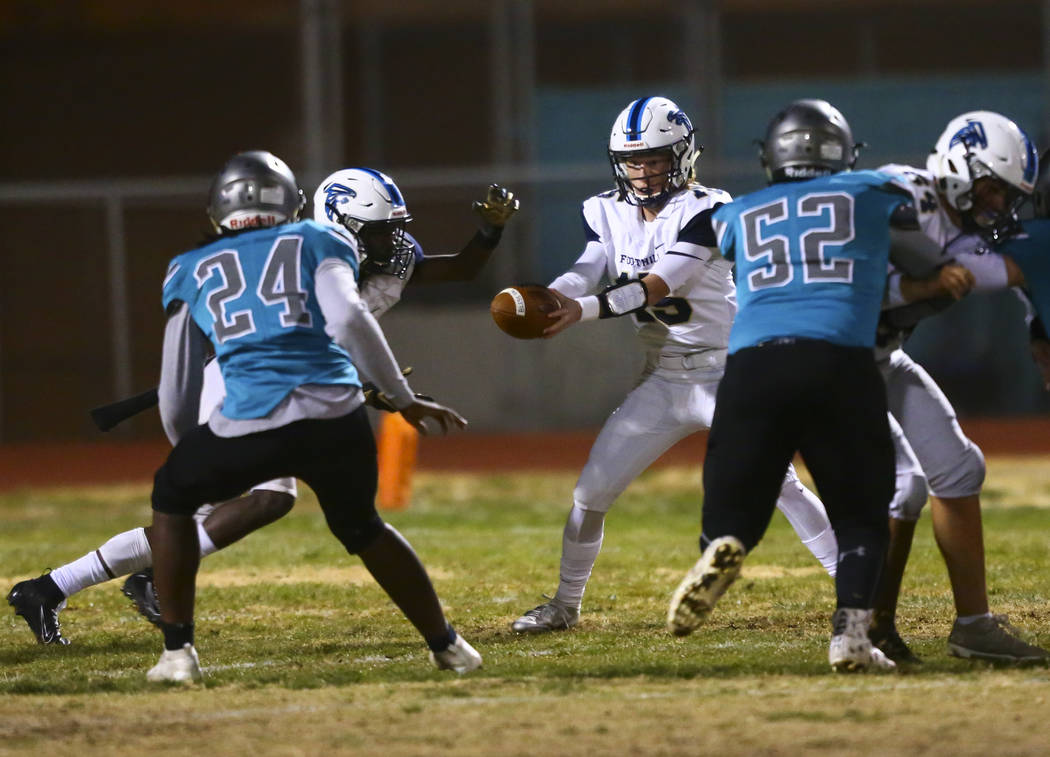 Foothill quarterback Koy Riggin (15) hands the ball off to Foothill's Kendric Thomas (2) during ...