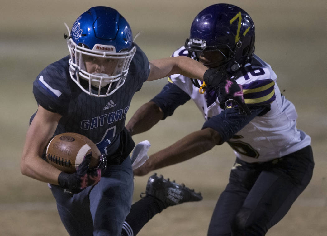 Green Valley's Brady Clayton (4) makes a reception past Durango's Michael Hayword (6) in the se ...