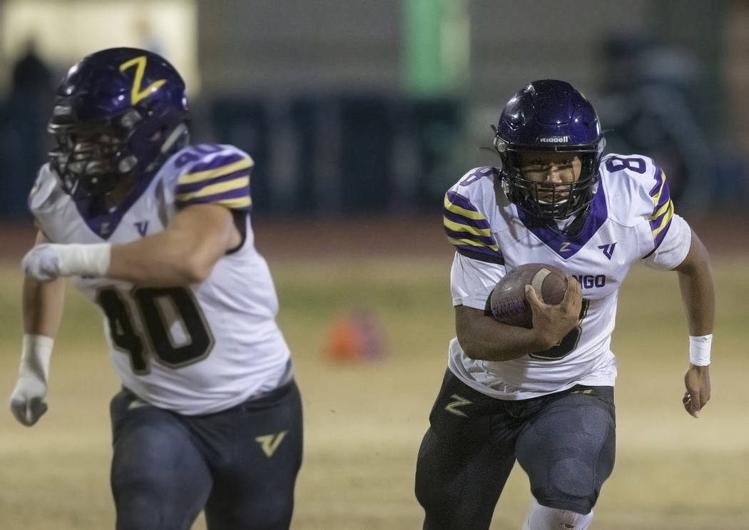 Durango's Ryan Cabase (8) scrambles for a first down with blocker Jayden Marquez (40) in the le ...