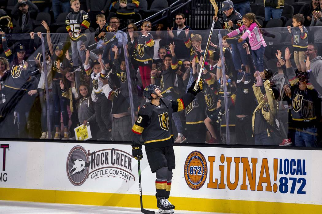 Vegas Golden Knights center Nicolas Roy (10) gives away his stick to a lucky fan after scoring ...