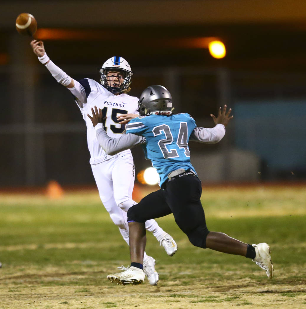 Foothill's quarterback Koy Riggin (15) throws a pass under pressure from Silverado's Kyrell Mcb ...