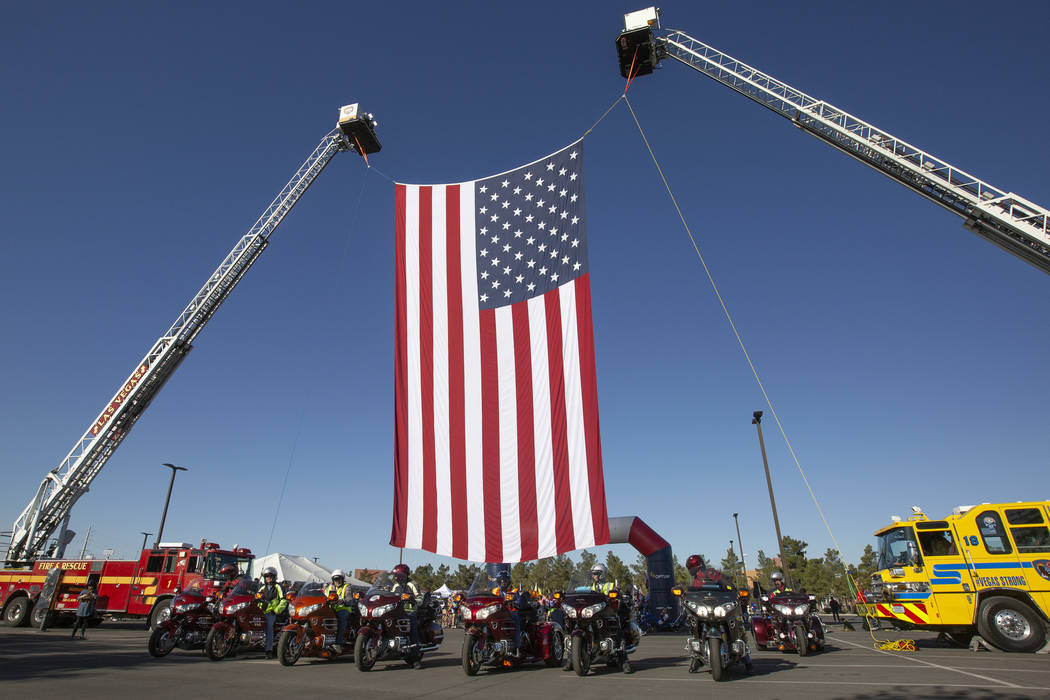 The American flag is hung for Las Vegas Honor Ride participants to ride under on Saturday, Nov. ...